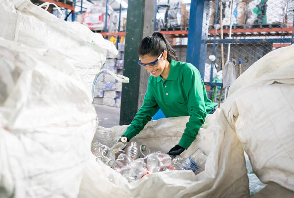 woman in a green shirt sorting plastic bottles in a waste management facility